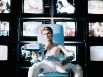 man-who-fell-to-earth-the-1976-006-bowie-seated-in-front-of-bank-of-televisions-00m-ezc-1000x750
